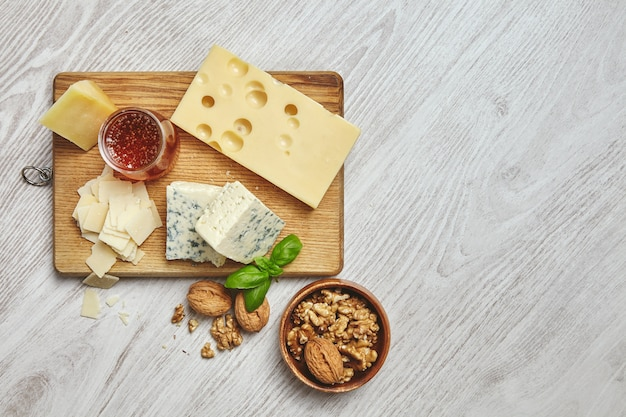 Set of four cheeses on rustic cutting board isolated on side of brushed white wooden table served for breakfast with rustic honey and walnuts in brown bowl with basil leaves. top view