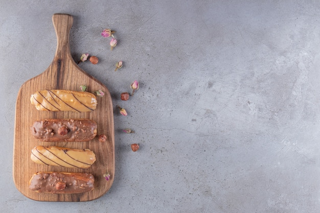 Set of four eclairs with various fillings on wooden cutting board