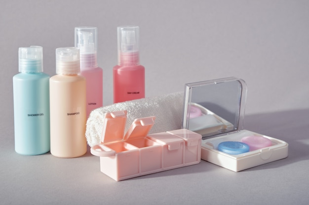 Set of four small plastic bottles for cosmetic products, kit for contact lenses, pill organizer and towel