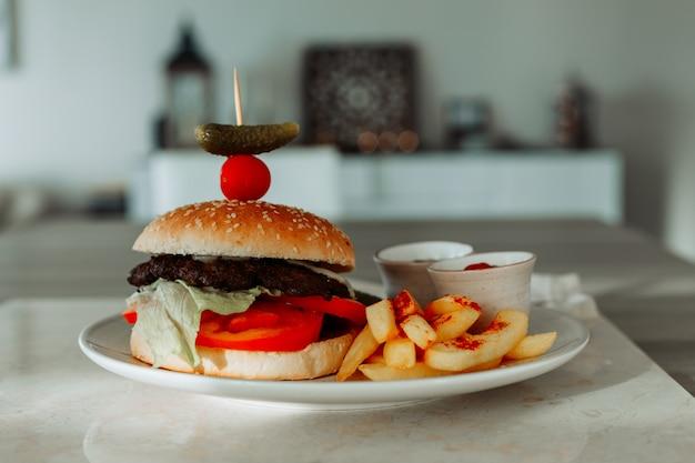 Insieme delle patate fritte e dell'hamburger in un piatto con la cucina e la tavola.