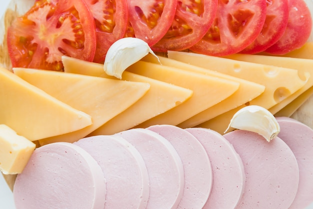 Set of fresh cheese near tomatoes and lunch meat