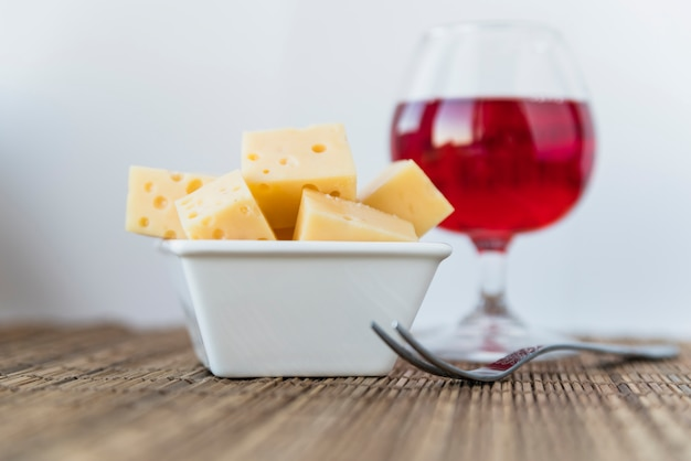 Set of fresh cheese in saucer near glass of drink