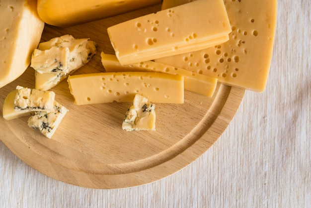 Set of fresh cheese on wood cutting board