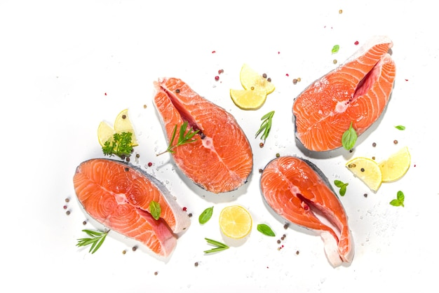 Set of fresh ready for cooking raw salmon steaks, red fish portioned slices with salt and spices, on white table background top view copy space