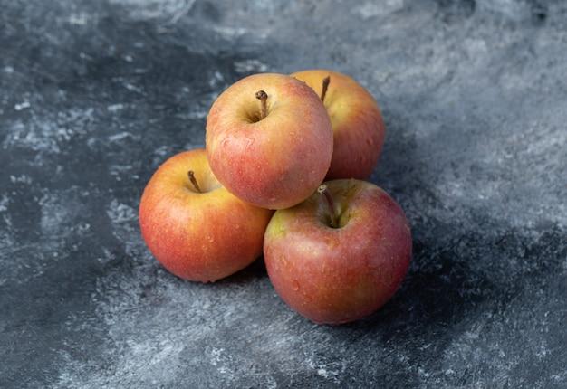 Insieme della mela gialla rossa fresca su fondo di marmo.