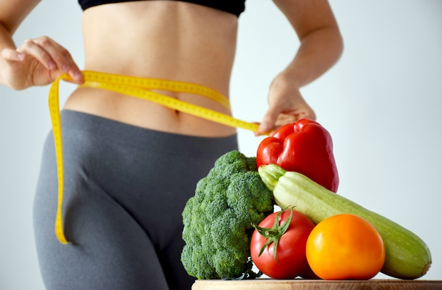 Set of fresh vegetables on cutting board with slim woman measuring her waist size with tape measure on background.