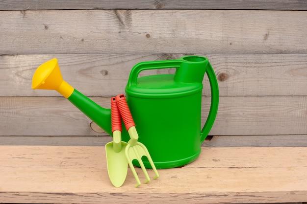 녹색과 주황색 손 도구에서 설정, 물을 나무 배경에 설 수 있습니다. 공간을 복사하십시오. 확대