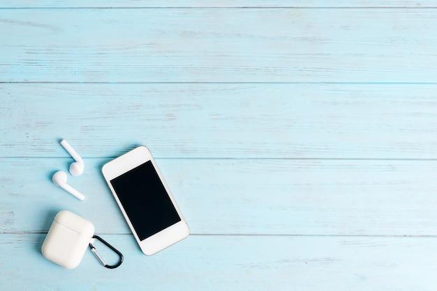 現代のスマートフォンと水色の木製の背景にイヤホンから設定します。上面図。