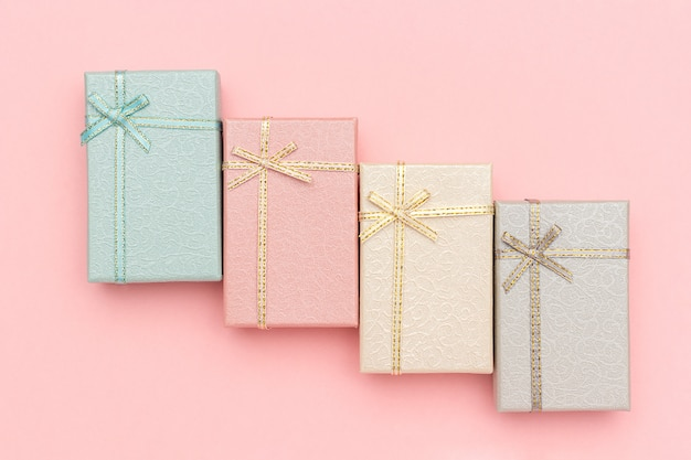 Set of gift boxes of pastel colors on pink background, top view