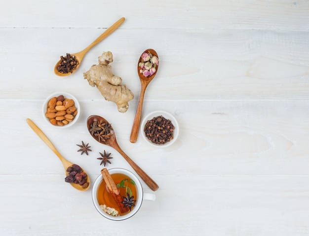 Set of ginger, herbs and spices and herbal tea on a white surface