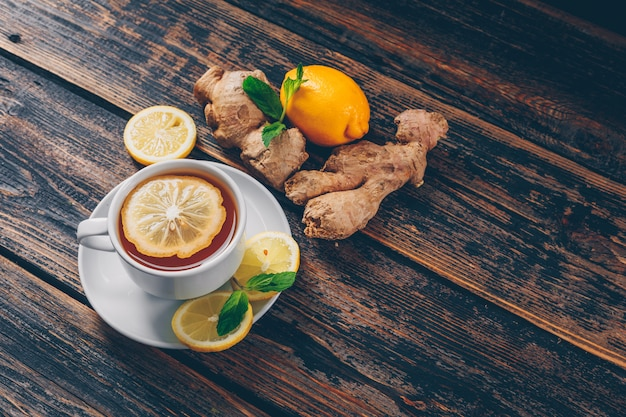 Set of ginger, lemon and a cup of tea on a dark wooden background. high angle view. space for text