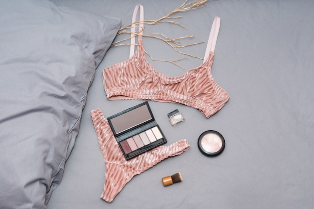 Set of glamorous stylish sexy lace lingerie with woman accessories on grey bedsheets