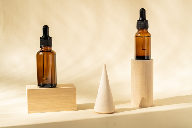 Set of glass bottles on wooden podiums for serum on beige surface