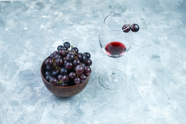Set of a glass of wine and black grapes in a clay bowl on a grungy grey background. high angle view.