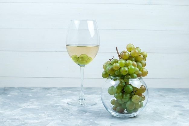 Set of a glass of wine and green grapes in a glass pot on grungy grey and wooden background. side view.