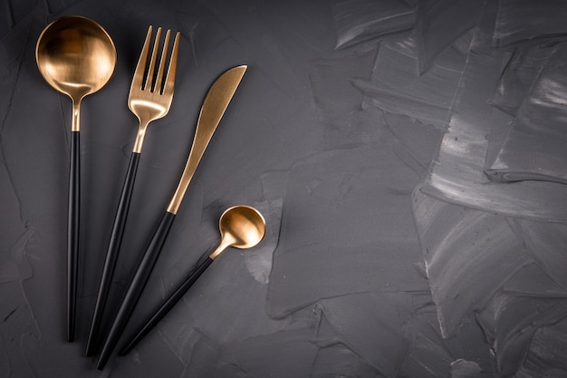Set of gold cutlery on gray table
