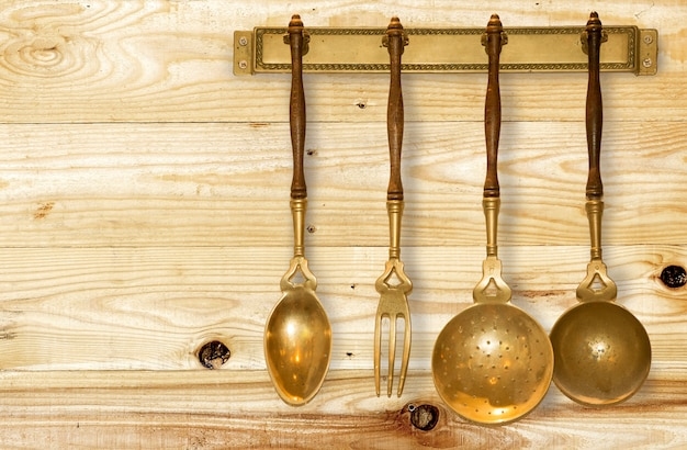 Set of gold vintage kitchen utensil hanging on wood background.