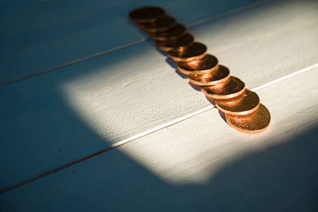Set of golden coins on board and sunshine in darkness