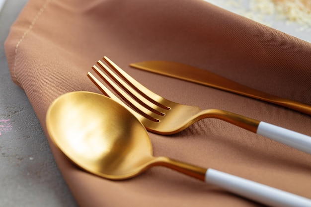 Set of golden cutlery on napkin close up photo