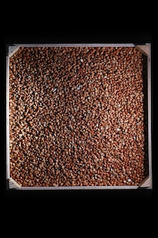 A set of grain cereals. rice, buckwheat and millet groats in a wooden tray. a grocery set of cereals. import of grain.