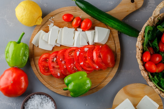 Set of green pepper, lemon, cucumber, salt and sliced cheese and tomatoes on a cutting board on a gray surface