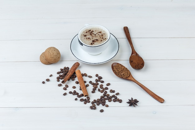 Set of grinded coffee, spices, coffee beans, cookies and coffee in a cup on a wooden background. high angle view.