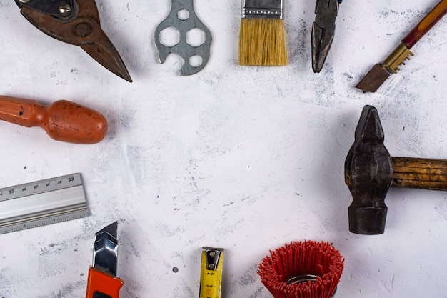 A set of hand tools on white marble background