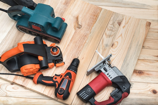 Set of handheld woodworking power tools for woodworking on light wooden. close up