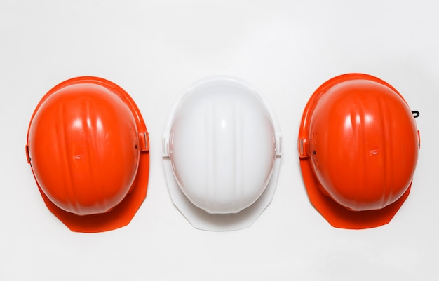 Set of hard hats. two orange and one white.