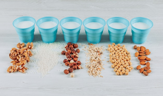 Set of hazelnuts, almonds and several nuts and cups of milk on a white wooden background. high angle view.