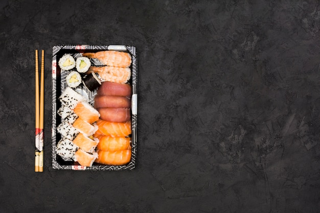 Set of healthy asian rolls arranged in tray and sticks over black background