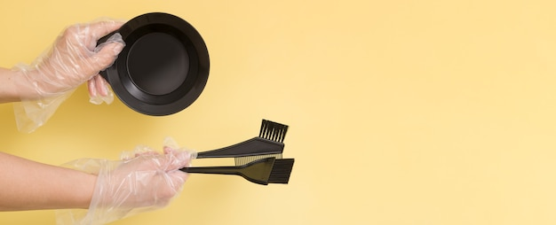 Set for home or salon hair dyeing in the hands of a woman with gloves. brushes and bowl for hair dye on yellow background. banner format with copy space
