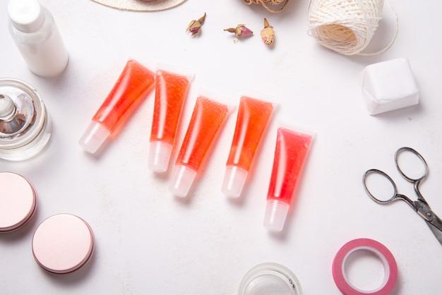 Set of homemade lip gloss on wooden desk