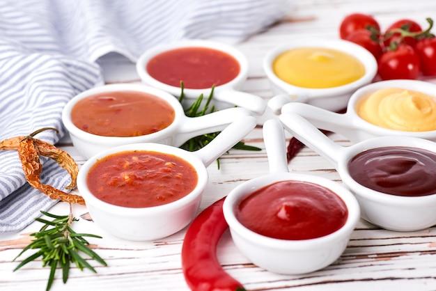 Set of homemade sauces - ketchup, mayonnaise, mustard soy sauce, bbq sauce, chimichurri, mustard grains.