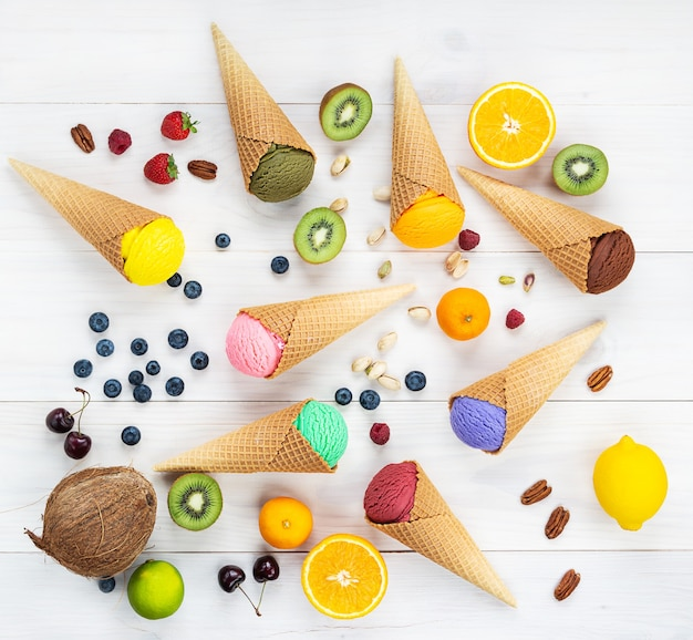 A set of ice creams of different types with fruits and berries on a wooden table