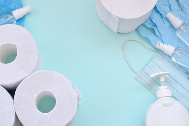 Set of important items for covid-19 quarantine. toilet paper, rubber disposable gloves with surgical face mask and hand sanitizer with liquid soap bottle on blue background