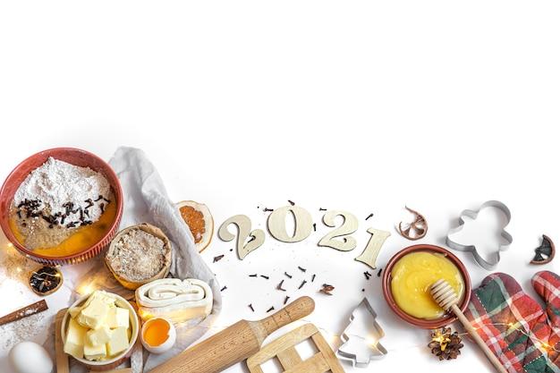 Set di ingredienti per fare una vista dall'alto di dessert festivo su uno sfondo bianco con un numero di legno per il prossimo anno.
