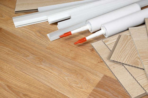Set of items for pvc ceiling indoor works. assembly adhesive bottles and pvc panels with plastic corners. indoor vpc siding kit. interior renovation works or construction materials