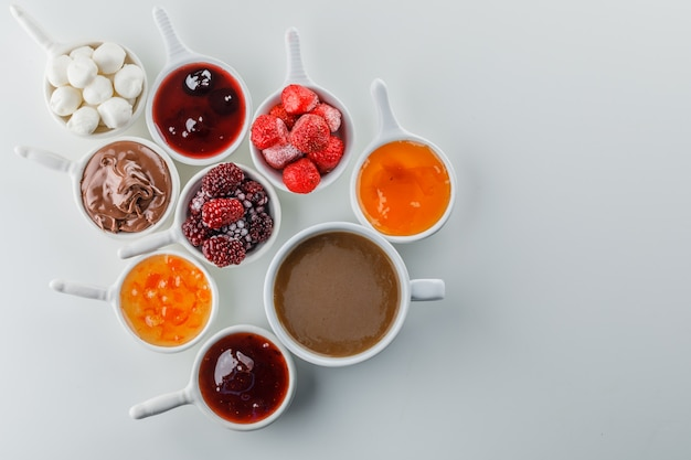 Set of jams, raspberry, sugar, chocolate in cups and a cup of coffee on a white surface space for text