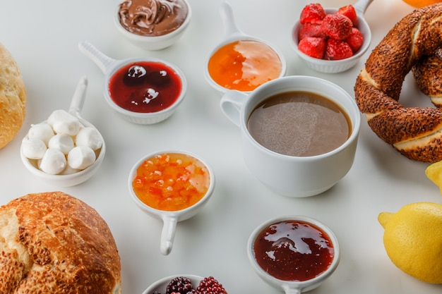 Set of jams, raspberry, sugar, chocolate in cups, turkish bagel, bread, lemon and a cup of coffee on a white surface