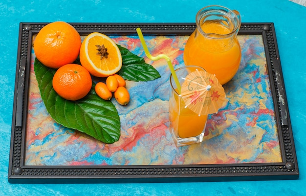 Set of juice in glasses, leaves, mandarin orange and oranges in a frame with abstract colors on cyan. high angle view.