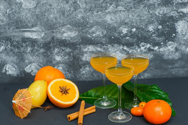 Set of juice in glasses, lemon, leaves, mandarin orange and oranges on dark and textured surface. side view.