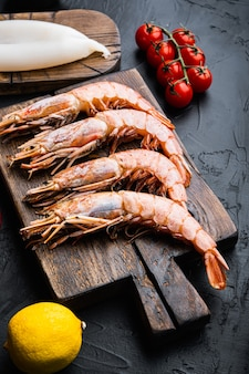 Set of king shrimps with ingredients for paella on black concrete surface, food photo.
