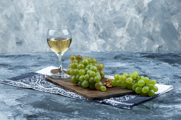 Set of kitchen towel, glass of whisky and white grapes on a cutting board on a dark and light blue marble background. close-up.