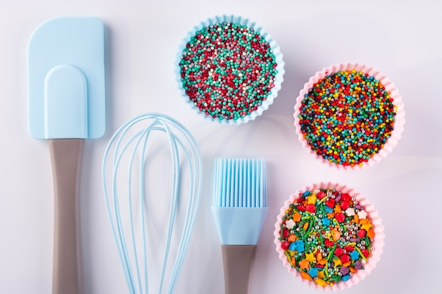 Set of kitchenware for cooking pastries and  rainbow sprinkles for decoration on white background