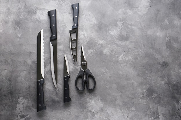 A set of knives. various kitchen utensils on gray table