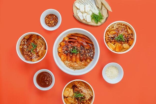 A set of korean food is served warm on the orange background.