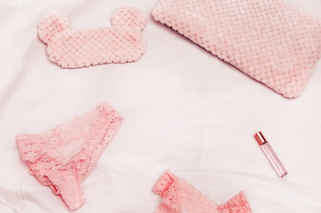 Set of lace underwear, sleep mask, perfume on white cotton sheet. accessories for woman. romance lifestyle and pink dreams. top view and copy spsce.