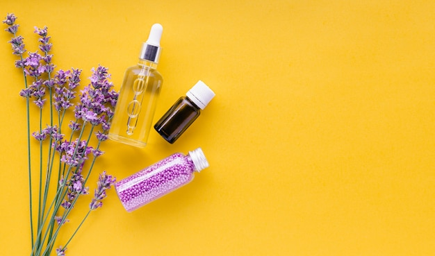 Set lavender skincare cosmetics products natural spa beauty products fresh lavender flower herbs on yellow background lavender essential oil serum cream bath beads flat lay copy space