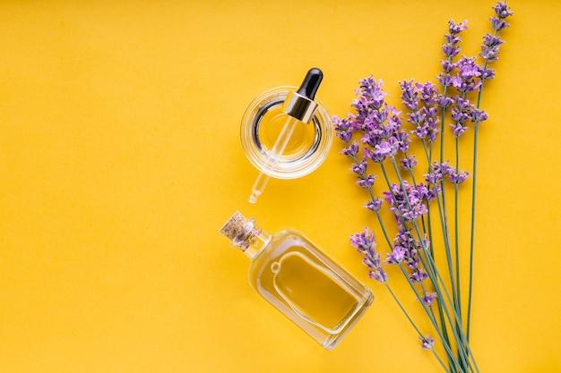 ラベンダースキンケアオイル化粧品をセットします。ナチュラルスパ美容製品黄色の背景に新鮮なラベンダーの花のハーブ。ガラス瓶に入ったラベンダーエッセンシャルオイルセラム。フラットレイコピースペース。